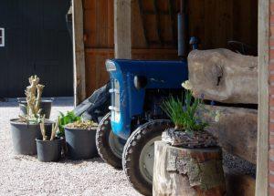 De voorkant van een blauwe tractor op een boerderij in Twente.