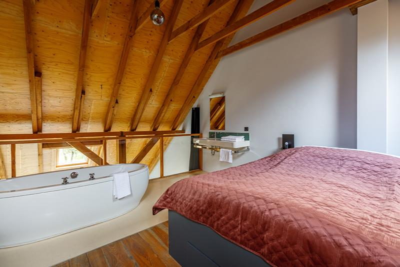 De slaapkamer met ligbad van de groepsaccommodatie in Delden.